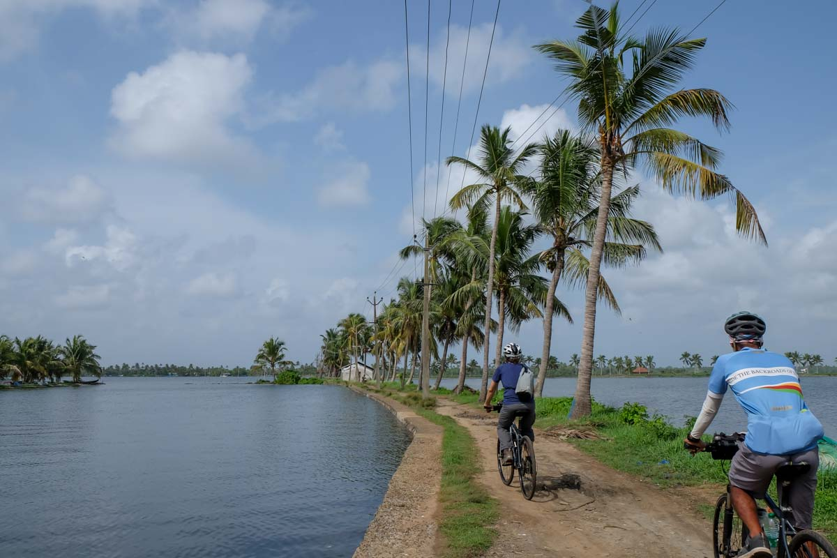 Riding along small canals during a Kochi backwaters bicycle tour