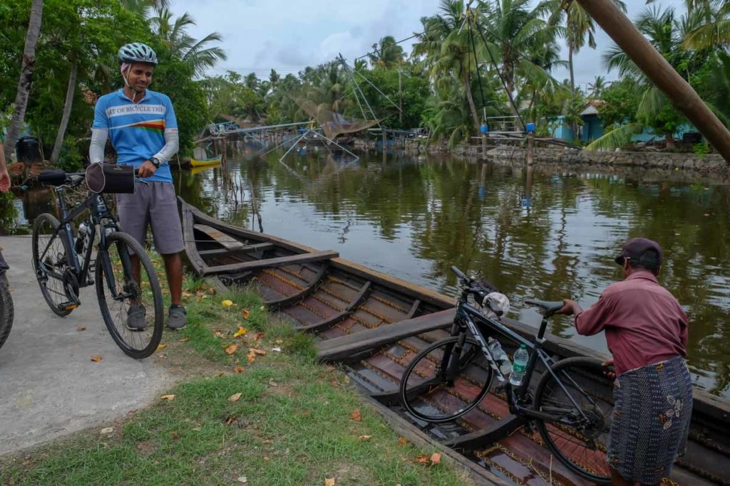 Dibin and the boatmen load our bicycles in a traditional Kerala wooden longboat