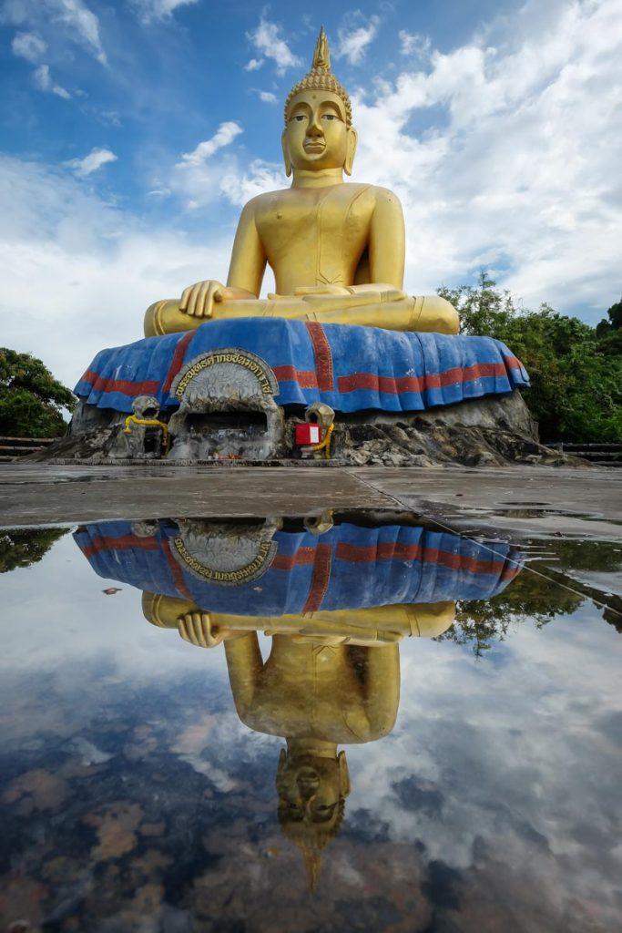 Golden Buddha statue reflected in a pool in Thailand.